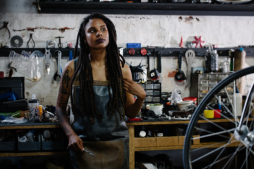 Candid portrait of afro-american bicycle mechanic standing in he